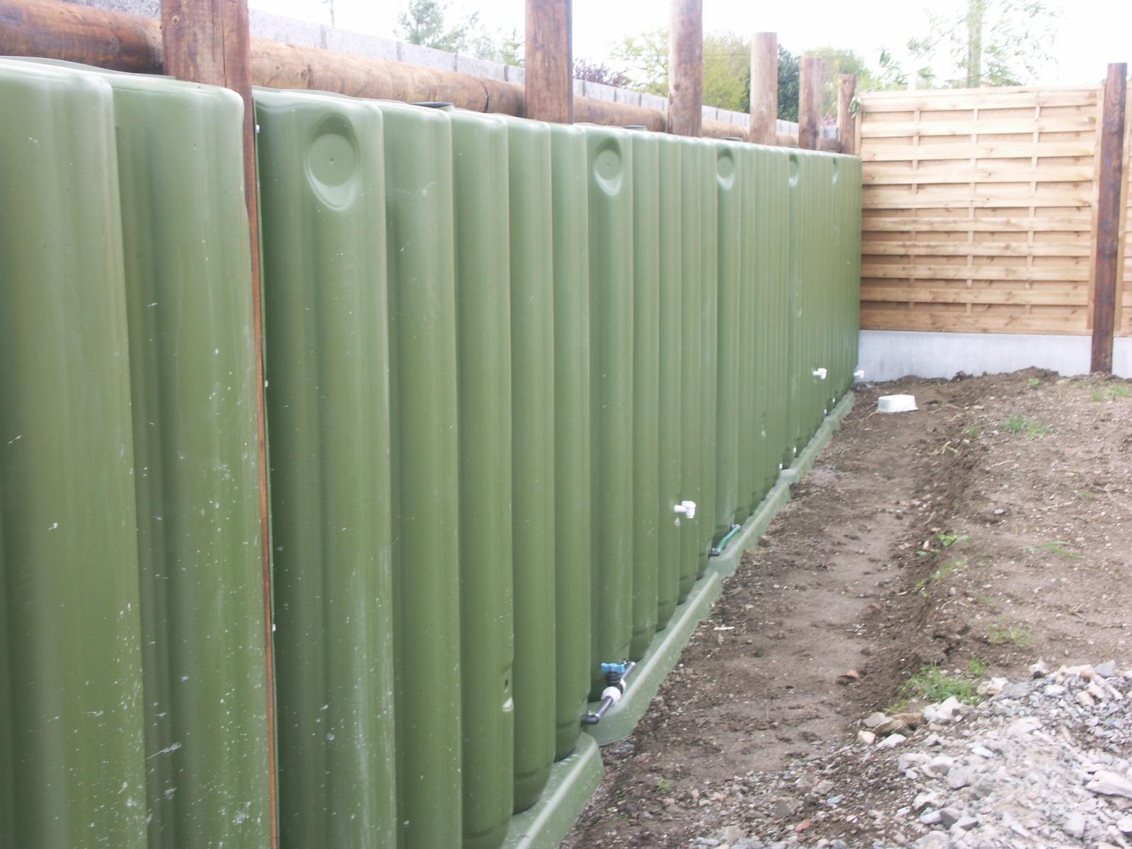Cuve de récupération d'eau de pluie en clôture.