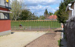 Clôture et réserve d'eau en bordure d'un jardin pédagogique