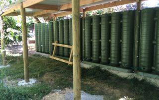 Cuves de récupération d'eau de pluie servant de mur d'un abri bois