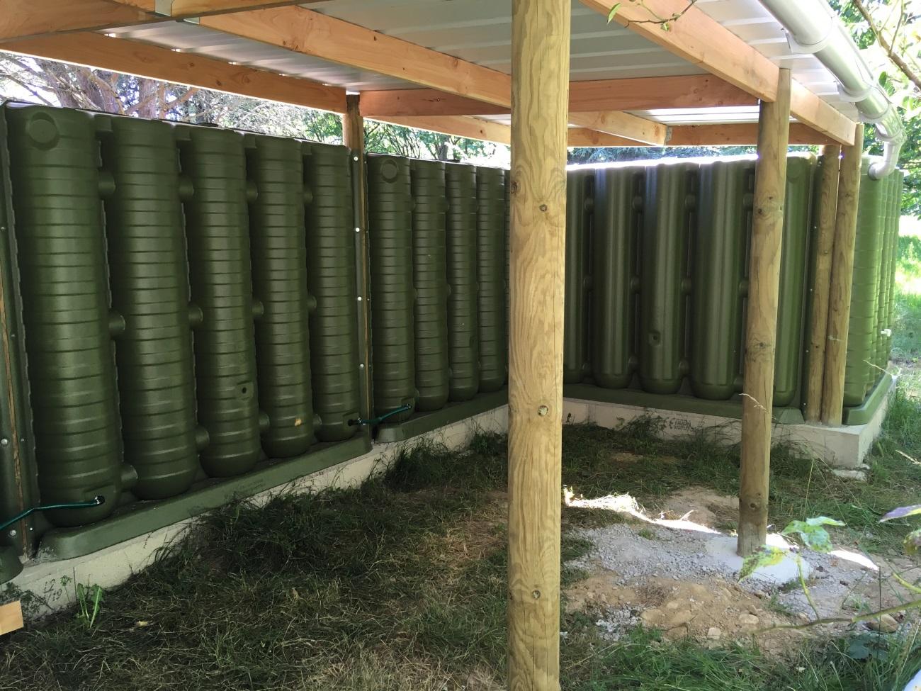 Récupérateurs d'eau de pluie servant de mur pour un abri bois