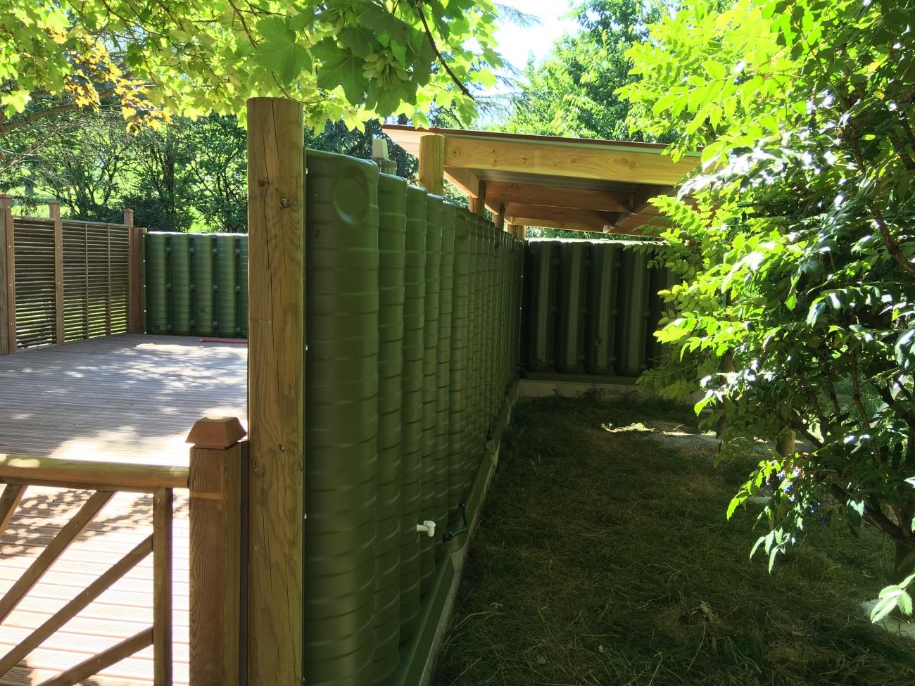 Récupérateurs d'eau de pluie intégrés dans un abri bois et une terrasse